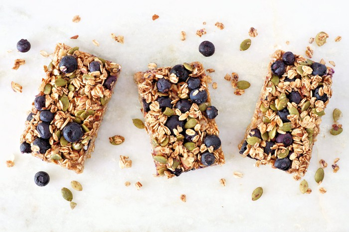 Three healthy granola and fruit snack bars on a marble table.