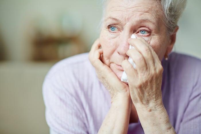 Senior woman wiping away tears