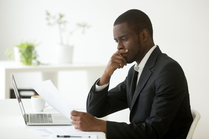 A man with his hand to his chin sits at a desk with a laptop.