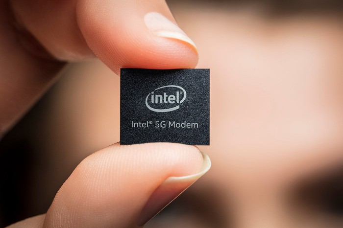 """A person holding a chip that has etched on it """"Intel 5G Modem"""""""