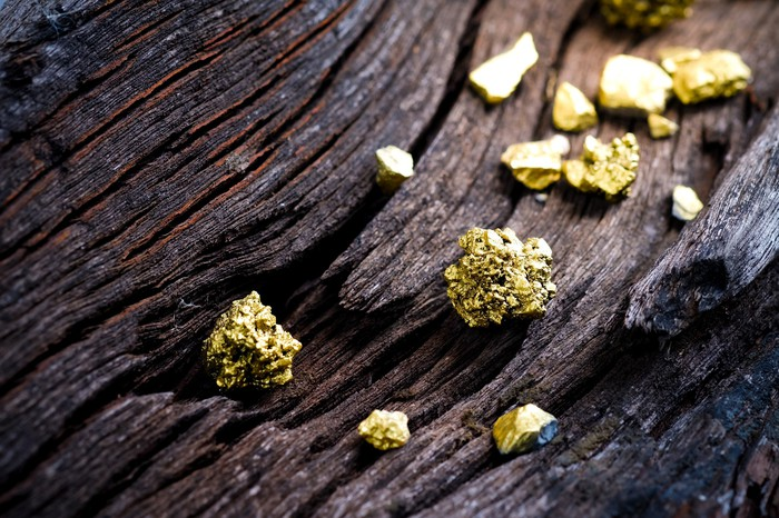 Pieces of gold ore on an old wooden rail.