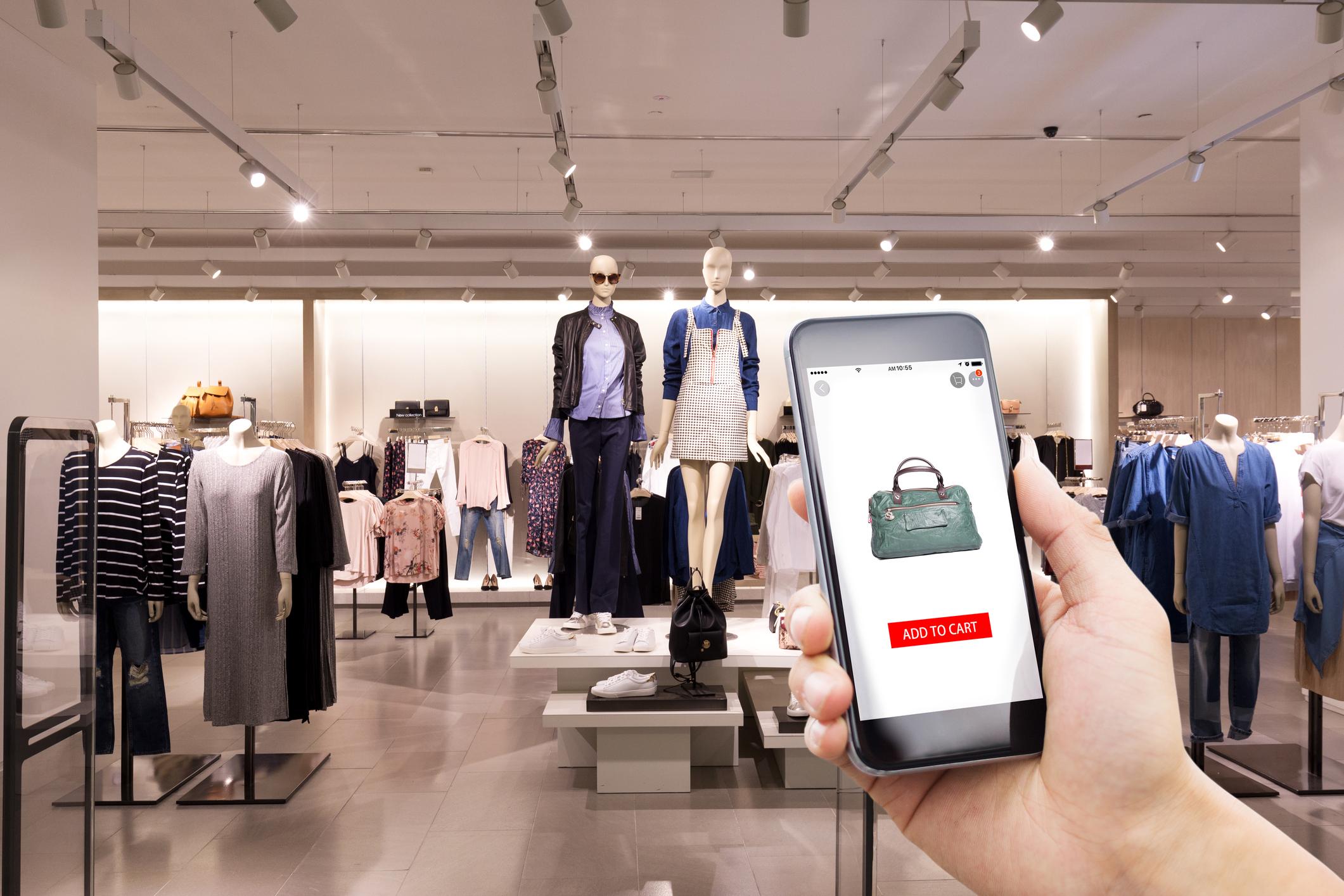 A shopper checks a handbag's price on a smartphone app.