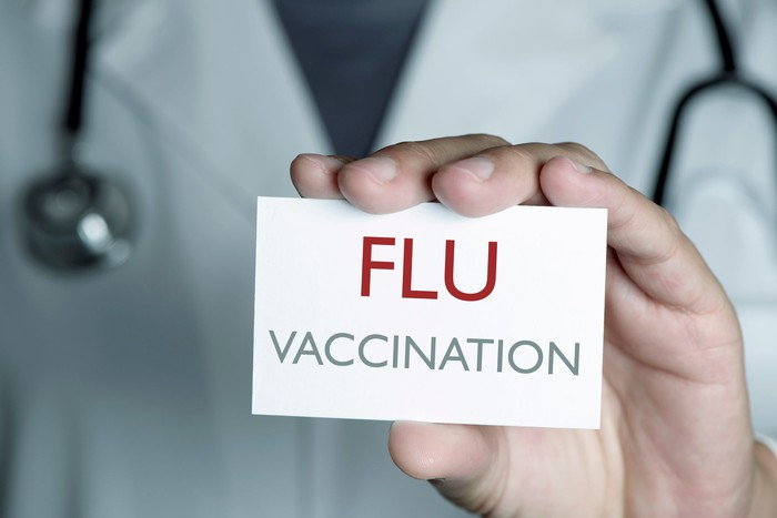 """Doctor holding out a signboard that reads """"flu vaccination""""."""