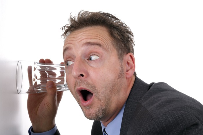 A man in a suit listens through a wall using a glass.