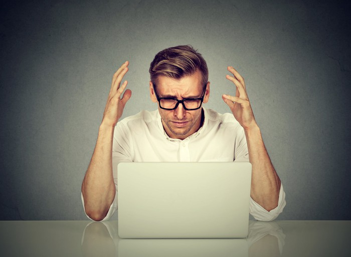 A man raises his hands in despair as he looks at the monitor on a laptop.