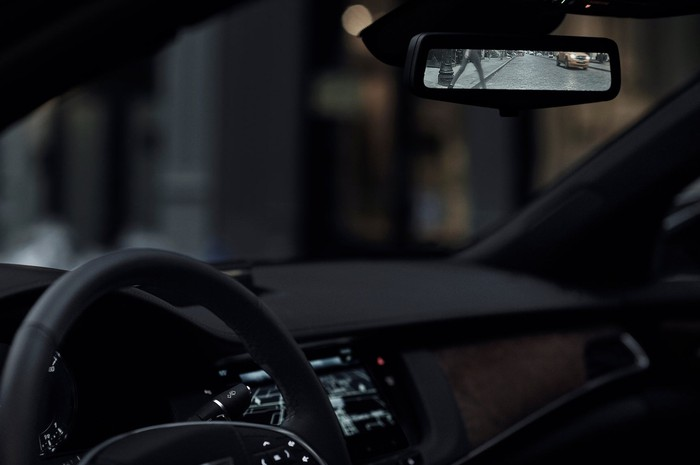 "A view of the center rear-view mirror in a Cadillac CT6, which is ""reflecting"" a rear view unobstructed by the car's roof pillars."