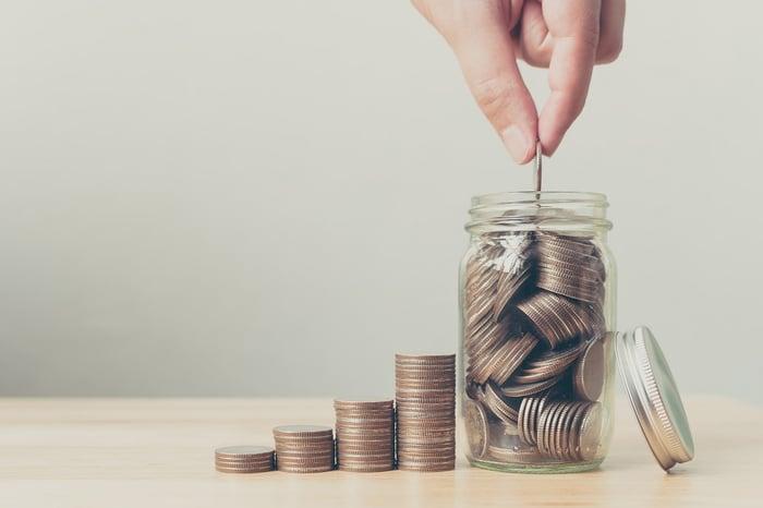 A hand placing a U.S. quarter into a jar full of quarters.