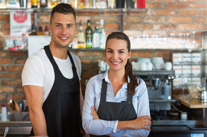 Smiling man and smiling woman in aprons