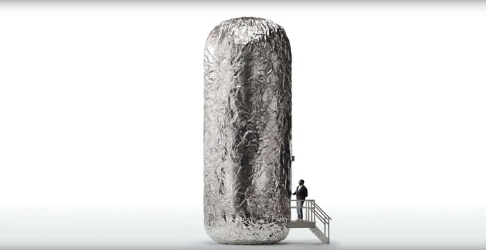 A man at a top of a small staircase looking up at a giant burrito.