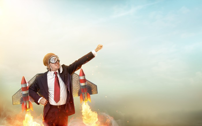 A man wearing a suit and a flight helmet and goggles raises his arm to the sky, as rockets strapped to wings on his back shoot out flames, suggesting an imminent launch.