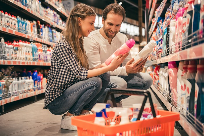 a young couple compares two household cleaners in a grocery store next to their basket full of items on the floor.