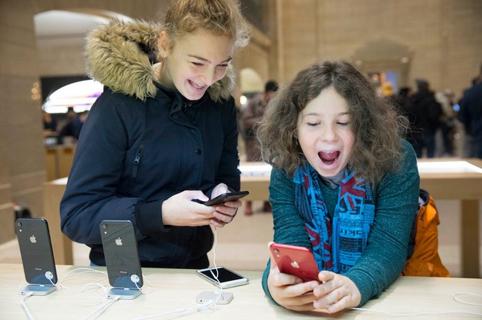 Two girls using iPhone XR devices in an Apple store.