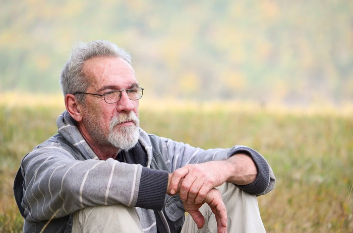 Older man with concerned expression sitting in an outdoor field.