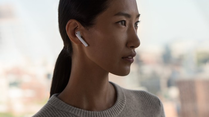 A woman wears AirPods in her ear in an Apple advertisement.