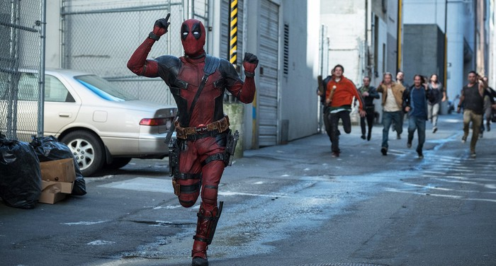 Deadpool runs down an alley.