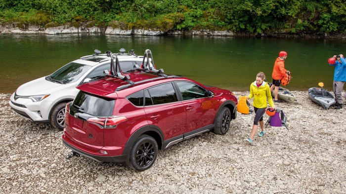 People three people next to a river with two kayaks and two Toyota RAV4s