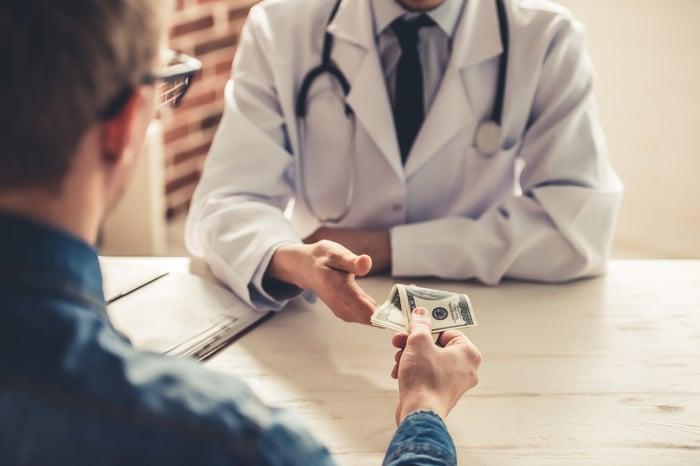 A man handing cash to a doctor behind a desk.