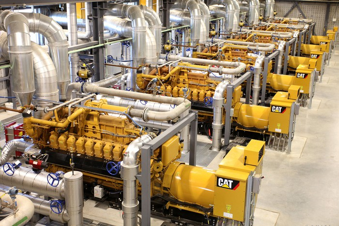 A row of Caterpillar engines in a factory environment attached to piping.