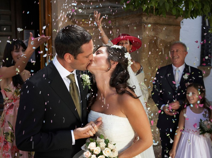 Bride and groom kissing while onlookers throw confetti