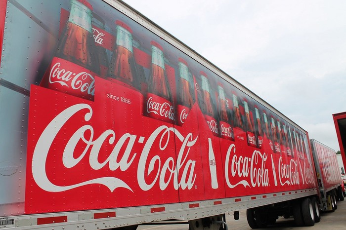 Semi trailer with pictures of bottles of Coca-Cola on its side.