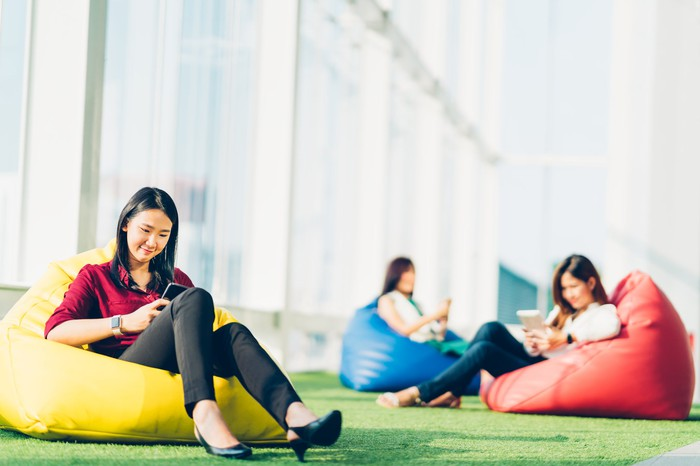 Three Asian women sitting on beanbag chairs while using mobile devices