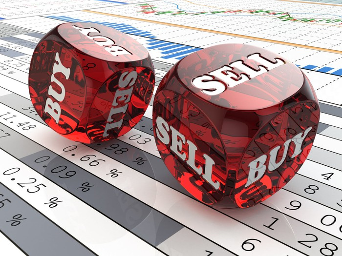"""Red dice that say """"buy"""" and """"sell"""" being rolled atop a piece of paper containing financial figures."""