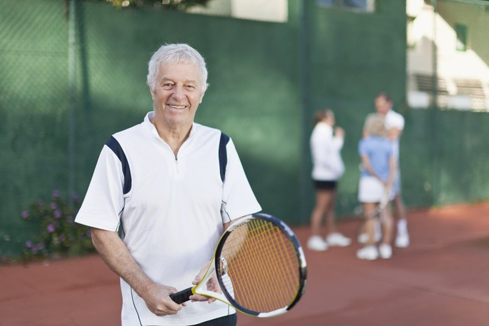 Smiling older man on tennis court holding tennis racket, with players in the background.