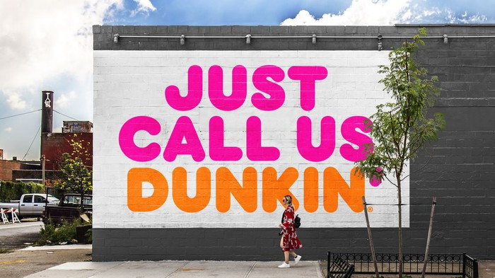 """Woman walking pass building mural with the slogan """"Just Call Us Dunkin'"""" in Dunkin' Brands logo colors of orange and purple."""