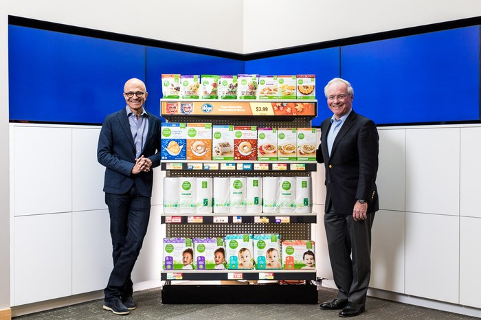 Microsoft CEO Satya Nadella and Kroger CEO Rodney McMullen pose in front of a shelf of Kroger Simple Truth products.