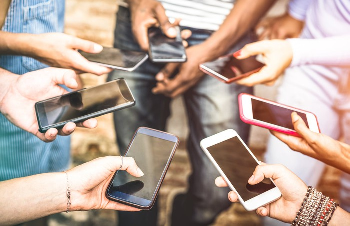 A group of friends using their smartphones in a circle.