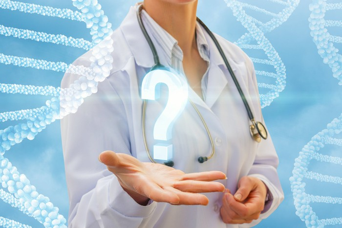 Physician with stethoscope around her neck holding palm out with a question mark appearing over it and cloudy wisps in the shape of DNA helixes in the background