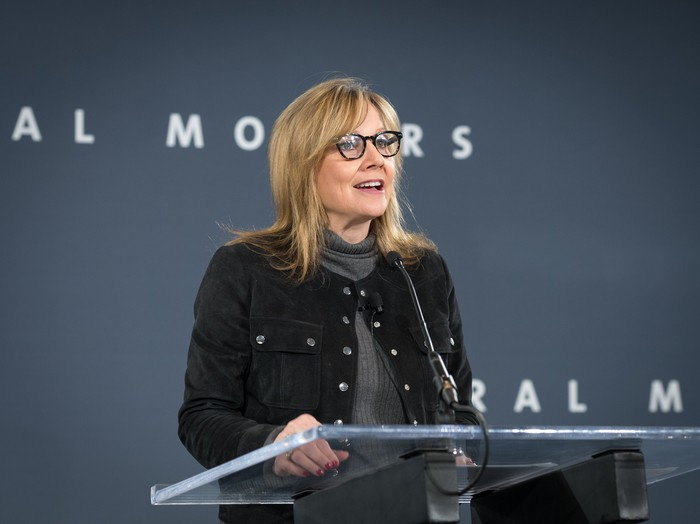 GM CEO Mary Barra standing at a podium in front of a dark-blue General Motors backdrop.