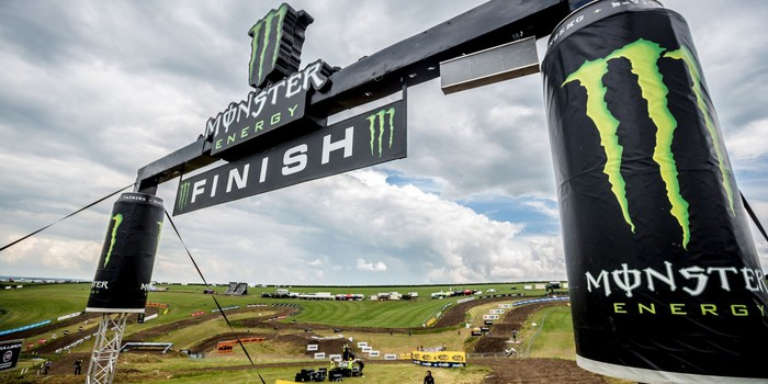 The finish line of a motocross race, featuring oversized Monster cans and many copies of the green-on-black clawmark logo.