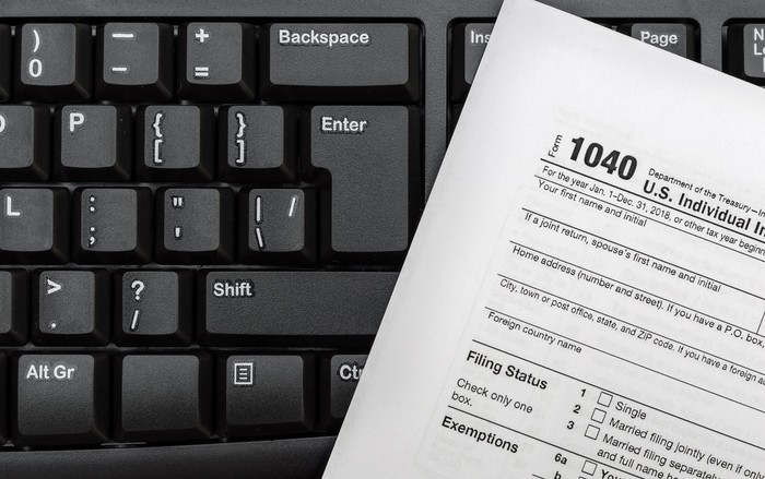 Tax Form 1040 resting on computer keyboard.