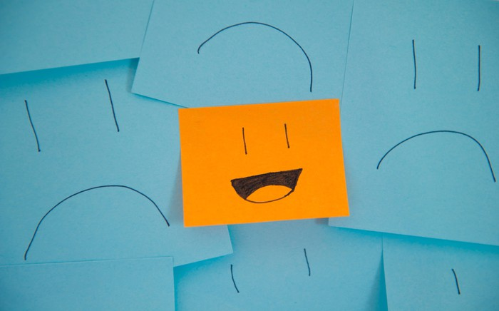 Blue sticky notes with sad faces with one orange sticky note with a smiley face