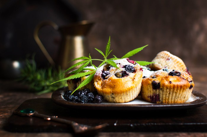 Marijuana leaf on top of blueberry muffins.