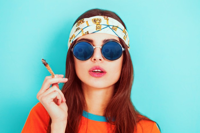 A young woman wearing a bandanna and sunglasses and smoking a joint.