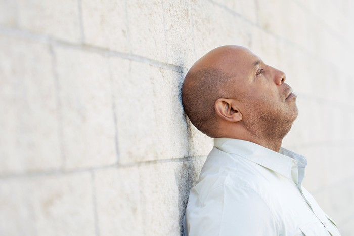 Man with sad expression leaning against a wall