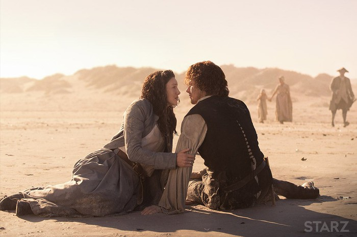A man and woman sitting on the ground in the desert facing each other.