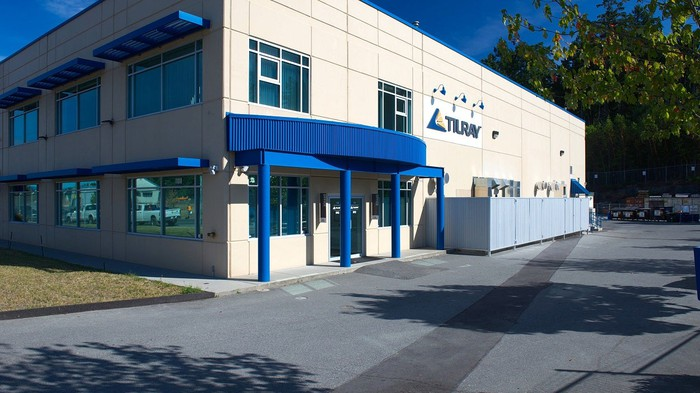 Two-story office building with Tilray logo on the side and blue entrance-way on a beige siding.