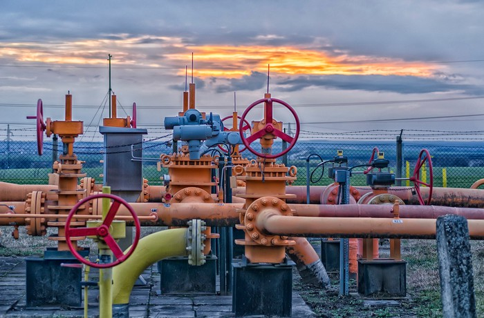 A natural gas field with pipeline valves and the sun setting in the background.