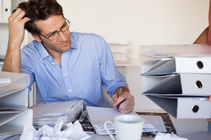 Man at cluttered desk scratching his head while taking notes