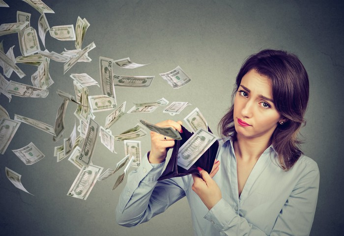 Woman holding a wallet open with numerous bills flying out of it