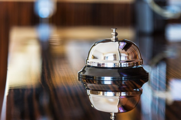 Gleaming service bell on polished wooden hotel lobby desk.