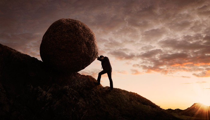 Man in a business suit pushing a boulder up a hill
