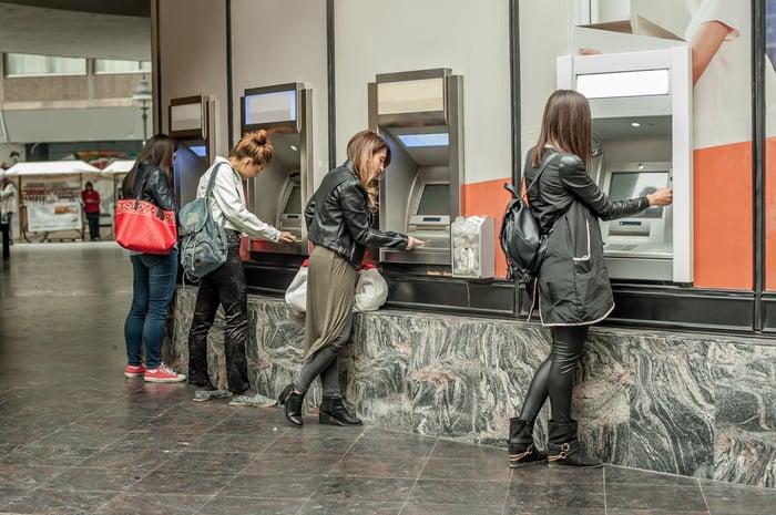 Four women using four ATMs