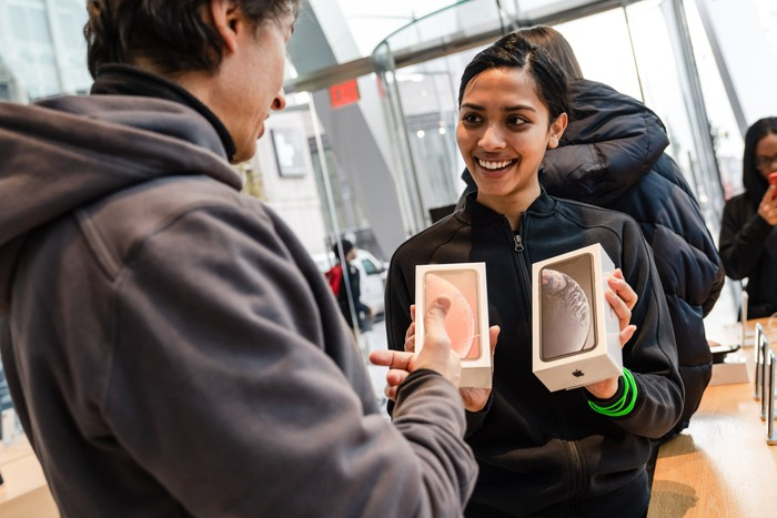 Woman in Apple store, holding up two iPhone boxes and smiling