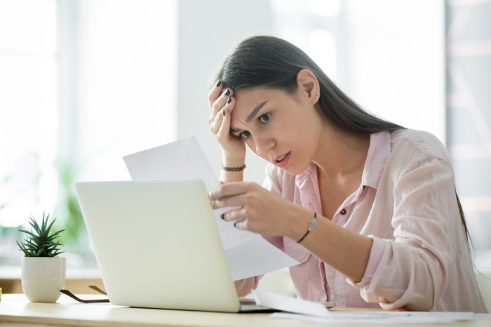 Woman at laptop looking at sheet of paper with stressed expression.