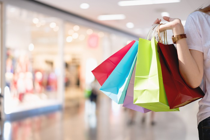 A woman's arm holding up several shopping bags in different colors in a shopping mall.