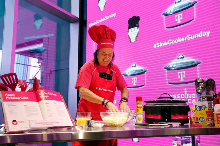 T-Mobile CEO John Legere in a chef's hat and apron cooking.